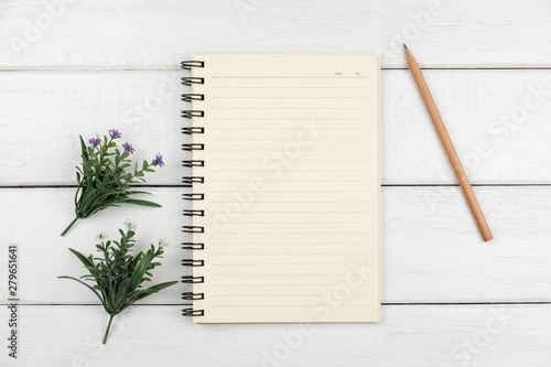 Top view of an open notebook with pencil on white wooden desk