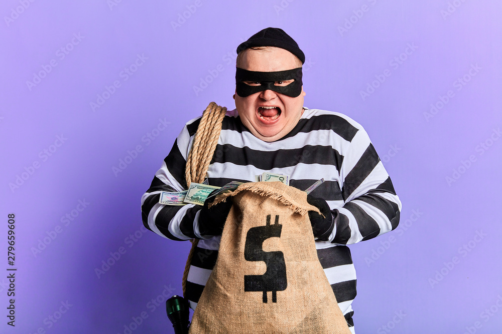 Fototapeta cruel guilty thief holding a sack and loking at the camera. isolated blue background. studio shot.profitable deal.
