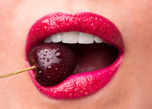 Red Lipstick On Lips And A Cherry With Water Droplets. The Girl Is Eating Cherry.