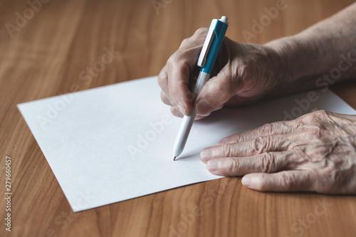 Obraz na plátně  Pensioner writes in pen on paper