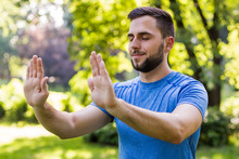 Handsome Man Exercising Tai Chi In The Park.