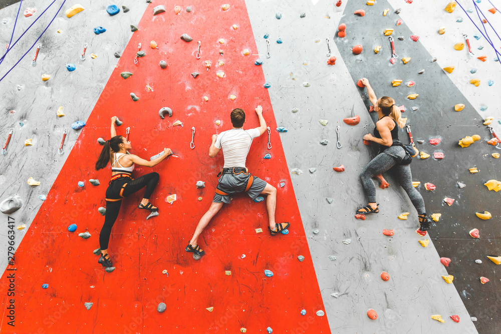 Fototapety, obrazy: Athletes climber moving up on steep rock, climbing on artificial wall indoors. Extreme sports and bouldering concept