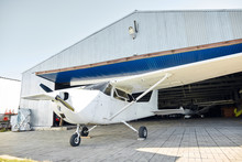 White Single-engine Airplane On Three Wheels Stands Before Small Aircraft Hangar Building, Prepares To The Flight, Parked And Ready To Take Off