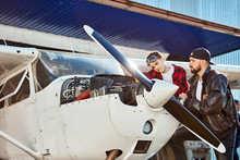 Father In Black Leather Jacket And His Little Son In Red Shirt And Aviator Glasses Making Final Check Up Together On Their Own Private Light Propeller Air Jet, Hangar Building On The Background.