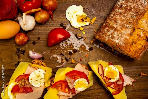 Sandwich preparation photo: bread loaf, vegetables (tomato, onions, garlic), eggs, plate with ready sandwiches on a wooden background © Piotr