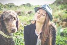 Frühling: Elegante Junge Frau Mit Hund, Pudel Und Hut Und Kussmund, 20 - 30 Jahre Alt, Genießt Mit Ihrem Pudel, Den Sonnenschein Im Garten.