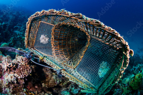 Fotografia An abandoned underwater fish trap resting on corals on a tropical reef in Asia
