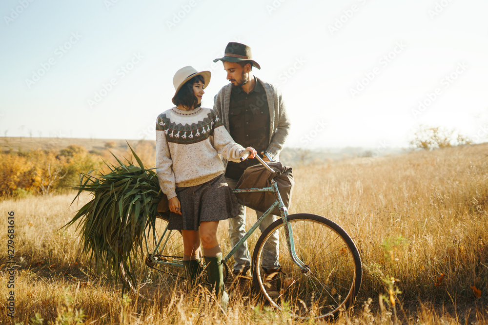 Fototapety, obrazy: Lovely hipster couple with bike . Couple wearing beautiful hats and sweaters. Lifestyle, happy couple of two play on a sunny day in the park. The concept of youth, love and lifestyle. Sunset in autumn