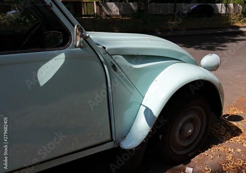 Tela Hellblaue französische Oldtimer Limousine steht am Straßenrand.