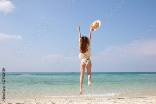 Cute woman with Bikini jump up on beach expressing  hapiness and enjoyment Canvas Print