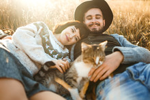 Lovely Hipster Couple With Cat. Couple Wearing Beautiful Hats And Sweaters. Lifestyle, Happy Couple Of Two Play On A Sunny Day In The Park. The Concept Of Youth, Love And Lifestyle. Sunset In Autumn.