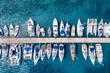 canvas print picture - Luftaufnahme einer Marina mit zahlreichen Segelbooten und Yachten über türkisblauem Meer