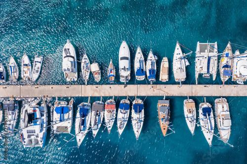 Widok z lotu ptaka mariny z licznymi żaglówkami i jachtami nad turkusowym morzem