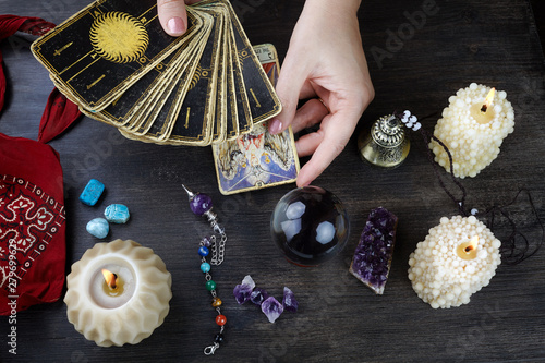 Fortune teller female hands and tarot cards on dark wooden table Canvas Print