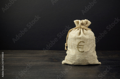 A full bag of dollars on a dark table Wallpaper Mural