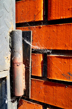 Old Rusty Door Hinge With A Spider Web On A Red Brick Wall.