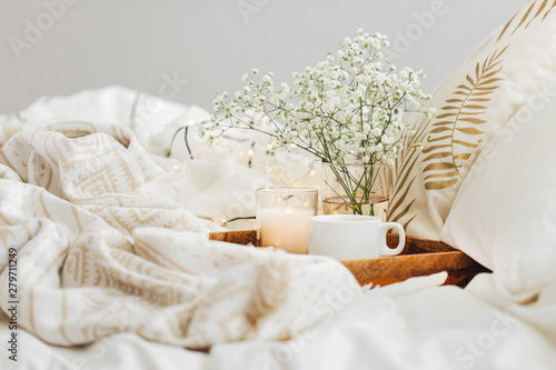 Obraz na plátně Wooden tray of coffee and candles with flowers on bed