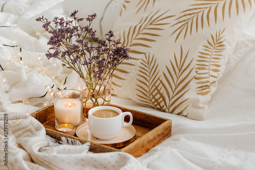 Fototapeta Wooden tray of coffee and candles with flowers on bed. White bedding sheets with striped blanket and pillow. Breakfast in bed. Hygge concept. obraz