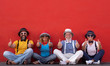 Leinwandbild Motiv Smiling group of four people sitting against a red wall enjoying friendship gesturing ok with hands. Relaxed and positive moment. Dressed with colorful caps, bow ties and suspenders