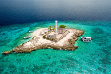Aerial View Of A Tiny Tropical Island With A Lighthouse Surrounded By A Huge Coral Reef (Capitancillo Island, Philippines)