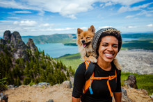 Girl Hiking With Dog In Backpack