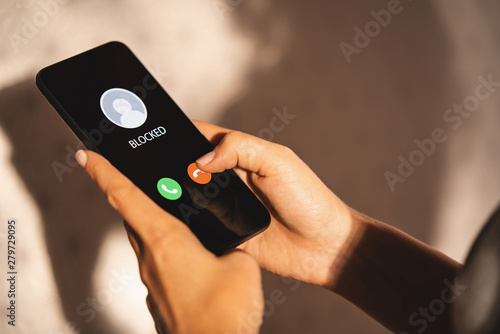 Fotomural  Woman Block a Phone Number or incoming Call from a anonymous stalker or Ex boyfriend