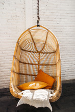 Wicker Rattan Hanging Chair In Loft Cafe. Eco Friendly Furniture Style And Concept. Orange Pillows And Soft Fur On Chair. Hipster Cafe.