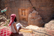 Asian Woman Traveler Sitting On Carpet Viewpoint In Petra Ancient City Looking At The Treasury Or Al-khazneh, Famous Travel Destination Of Jordan And One Of Seven Wonders. UNESCO World Heritage Site.