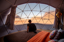 Asian Tourist Man Sitting On The Bed In Dome Tent Looking Outside At Wadi Rum Desert, Famous Natural Attraction In Jordan. Travel Middle East Concept