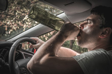 Drunk Driver With Bottle Of Wine Driving A Car