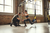Doing squat exercise. Confident young personal trainer is showing slim athletic woman how to do squats with Trx fitness straps while training at gym.