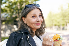 Stylish Charming Middle Aged Female In Black Leather Jacket Holding Cone Of Colorful Ice Cream Using Wooden Stick And Smiling At Camera, Enjoying Slow Summer Day, Walking Outdoors, Feeling Relaxed