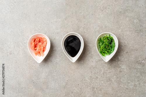 Obraz na płótnie Soy sauce, wasabi and ginger on stone table