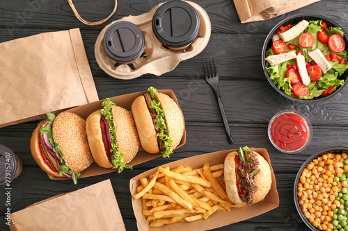 Different tasty food from delivery service on wooden background - 279757407