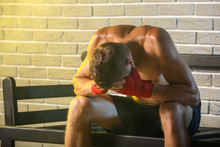 Upset Male Boxer Sitting On Bench Against Brick Wall