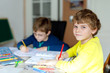 Leinwandbild Motiv Two little kids boys at home making homework. Little concentrated children writing with colorful pencils, indoors. Elementary school and education. Siblings and best friends learning.