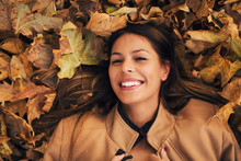 Smiling Girl On Autumn Leaves