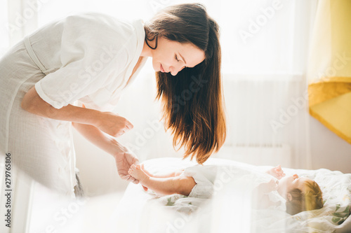 Obraz Adorable two month old baby girl lying on the bad. Mother holding daughter legs and smiling. Mother standing near the bed. Concept photo parenthood and motherhood. - fototapety do salonu
