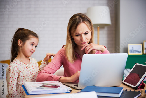 Girl disturbing her mother to work at home Canvas Print
