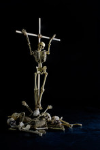 The Skeleton On Wooden Cross And Pile Of Bone On Dirty Dark Floor And Black Background