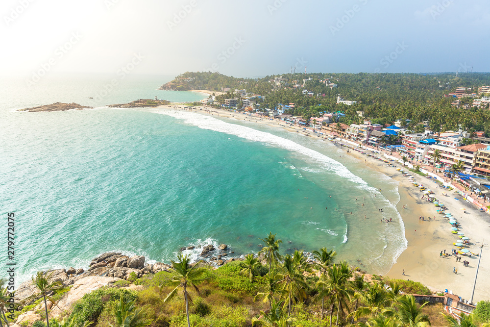 Fototapety, obrazy: Aerial view of tourists taking a dip in the turquoise waters of Lighthouse beach at Kovalam, Trivandrum. Tropical feel with green coconut trees and blue waters. India