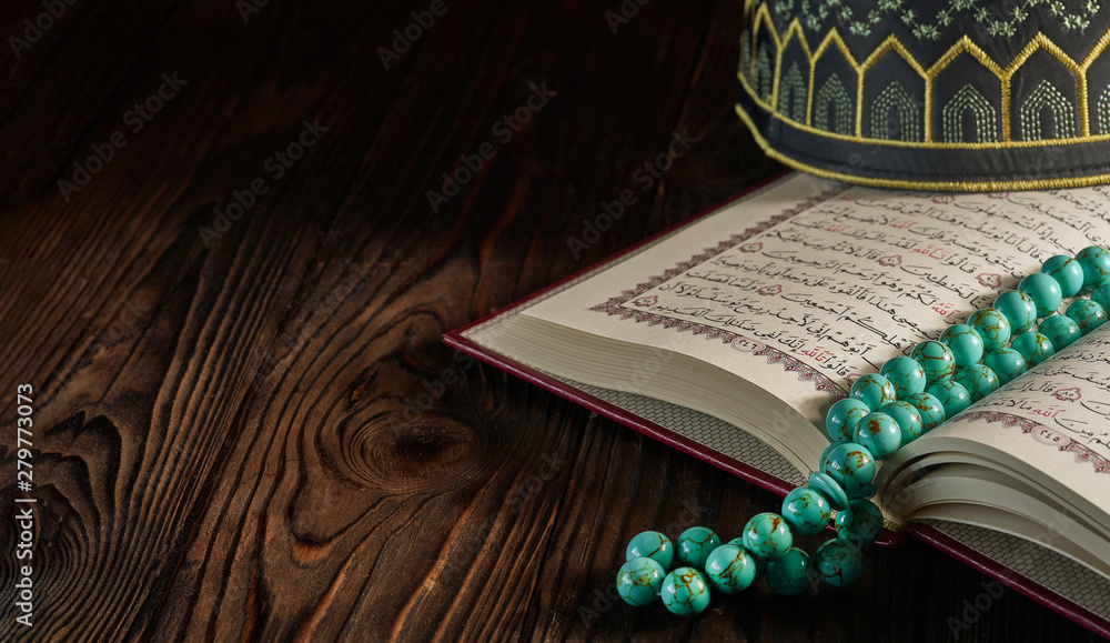 Fototapety, obrazy: Open Quran book with rosary beads and kopiah hat for muslims on wooden table
