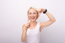 Photo Of A Cute Young Blonde Woman, Doing A Frame Gesture, Standing Over Isolated Background