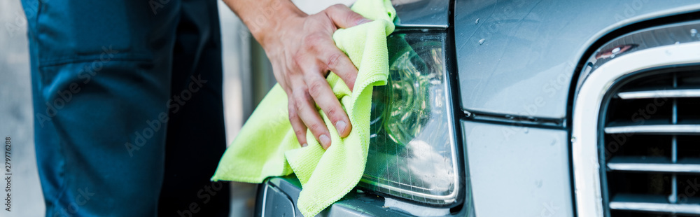 Fototapety, obrazy: panoramic shot of car washer holding green rag and cleaning car headlight