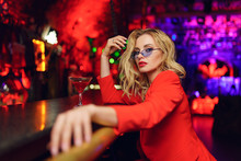 Photo Of Young Blonde Woman With Glasses And Red Suit Sitting At Bar With Cocktail Glass In Nightclub