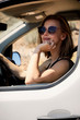 Road trip girl smiling in sunglasses from car, portrait