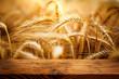Leinwanddruck Bild - Golden ears of wheat with wooden table