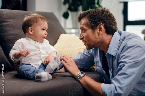 Fotografie, Obraz Mid adult father talking to his small son in the living room.