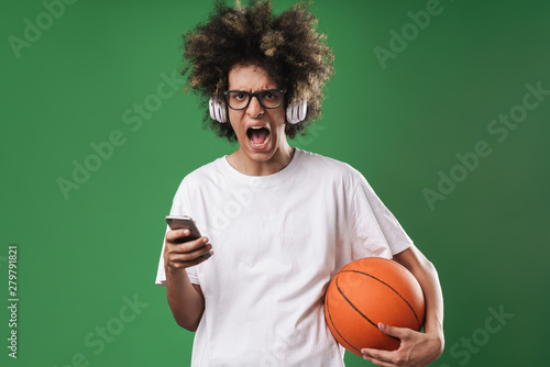 Portrait of irritated man with afro hairstyle playing using cellphone and headphones while holding basketball