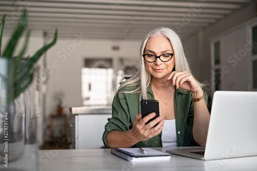 Fototapeta Stylish senior woman messaging with phone obraz